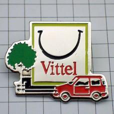 ピンバッジ・水ヴィッテル広告の前の赤い車